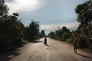 A woman and child walk across the main road of Pak Ok village, where the first case of surrogate motherhood was recorded.<br /> Lom Sak, Petchabun province, Thailand. Aug 24 2014<br /> Credit : Giorgio Taraschi for The New York Times