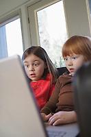 Young girls (5-6) on sofa using laptop surprised