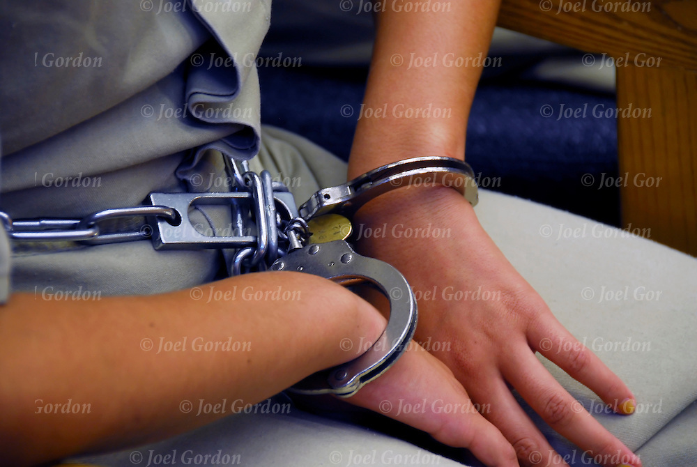 Caucasian female juvenile in handcuffed and leg irson sitting in the Juvenile Justice Center