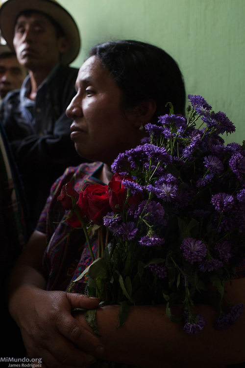 Magdalena Lopez Santiago, Ixil Mayan woman from Nebaj, holds flowers as she hopes to identify the human remains of her brother and parents, all killed in 1982. Ixil Mayan residents of Nebaj gather as the human remains of 36 war victims are returned to their surviving family members for a proper burial. Most of the victims, exhumed from mass graves in Xe'xuxcap, near Acul, starved in the mountainside while fleeing State-led repression in 1982. Most of the remains, exhumed by members of the Forensic Anthropology Foundation of Guatemala (FAFG) in 2013, were identified using DNA analysis and buried 35 years after their death. Nebaj, Quiché, Guatemala. February 2, 2017.
