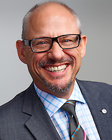 Corporate headshot plain light grey background featuring mature businessman in glass smiling warmly