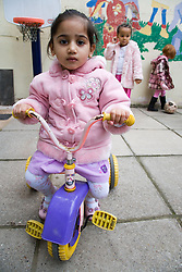 Little girl playing on a toy bike at breaktime,