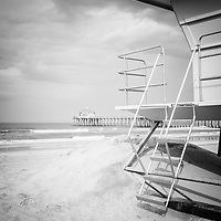 Photo of Huntington Beach Pier and lifeguard stand with storm clouds in black and white.