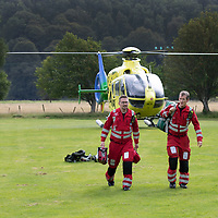 Helimed 76 the EC135 T2i Helicopter of Scotland's Charity Air Ambulance (SCAA) pictured after landing at Kinloch Rannoch with the backdrop of Schiehallion. Paramedics Daz O'Brien and Rich Garside are pictured leaving the helicopter<br />Picture by Graeme Hart.<br />Copyright Perthshire Picture Agency<br />Tel: 01738 623350  Mobile: 07990 594431
