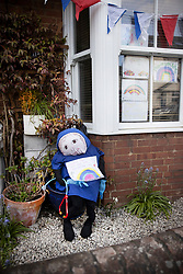 © Licensed to London News Pictures. 27/04/2020. Capel, UK. A scarecrow depiction of a nurse in uniform sits in the front of a house in the Surrey village of Capel. Residents of the village have resurrected their summer tradition of scarecrows in tribute to NHS medical staff and other key workers. Up to 30 of the life size home made doll like characters can be seen in front gardens throughout the village. The public have been told they can only leave their homes when absolutely essential, in an attempt to fight the spread of coronavirus COVID-19 disease. Photo credit: Peter Macdiarmid/LNP
