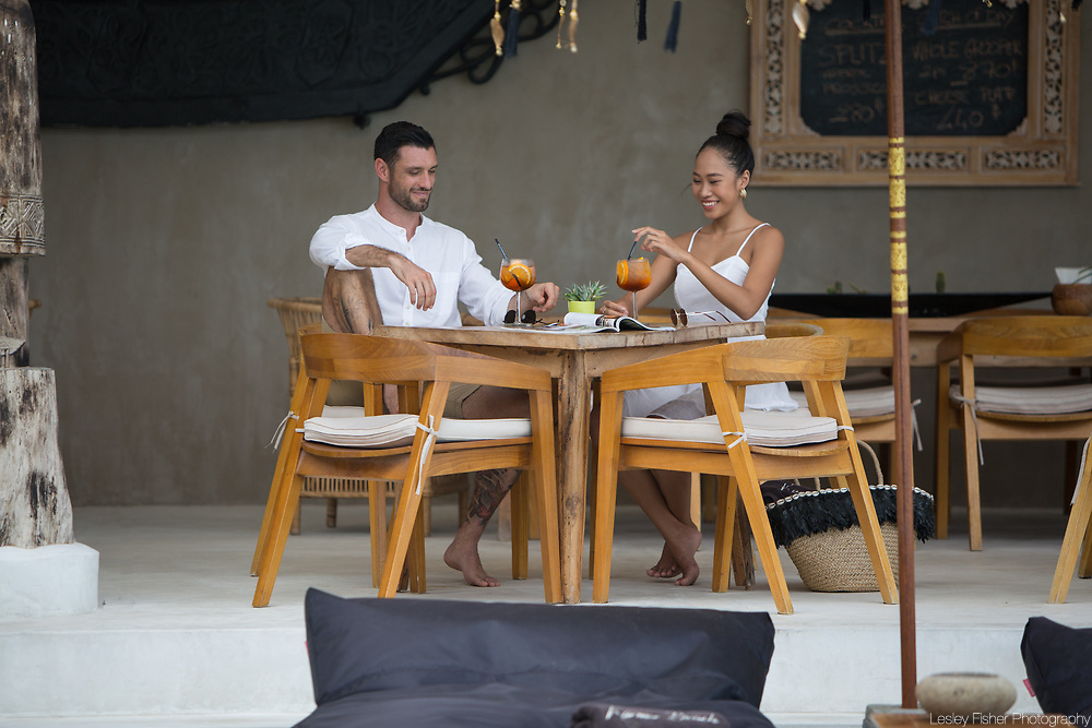 A couple relaxing and drinking an aperitif at the restaurat at Karma Beach Resort, a unique resort located on Bophut Beach, Koh Samui, Thailand