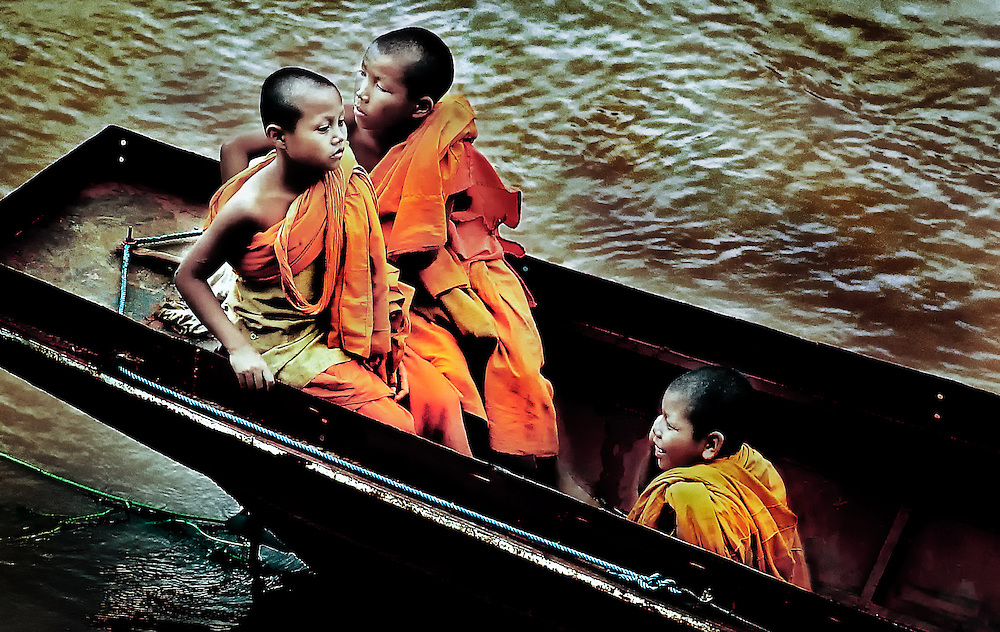 Buddhist novice monks crossing the Mekong river in Luang Prabang, Laos.