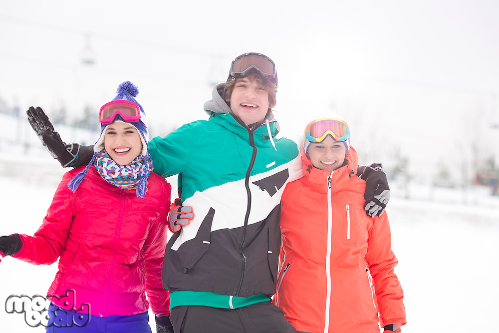 Portrait of young man with female friends enjoying in snow