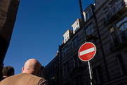 A bald-headed man walks below a no entry sign in central London.