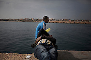 ITALY. Lampedusa:Tunisian migrants  take a rest  in the port of Lampedusa  on March  28, 2011. Copyright Christian Minelli.