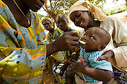 A woman gives a boy some of the oral re-hydration solution she just prepared outside the Adja-Ouere community health center in the village of Adja-Ouere, Benin on Friday September 14, 2007. The women come to learn on subjects like breast feeding or the preparation of oral re-hydration solutions. They later go back to their villages and give workshops on what they've learned.