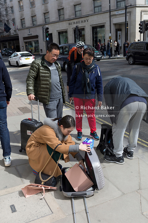 An Asian woman packs her suitcase with recent purchases, on 6th April 2018, in London, England.