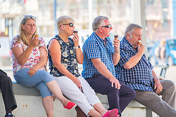 © Licenced to London News Pictures<br /> 02 July 2018 . Aberystwyth Wales UK<br /> <br /> UK Weather:  People relaxing in the shade with a cooling icecream  in Aberystwyth as the scorchingly hot  and very dry weather continues to dominate the UK.<br /> After a brief respite overnight, with some light rain, the searing heat has returned , with temperatures  again rising to the low 30º's this week<br /> <br /> photo credit Keith Morris / London News Pictures