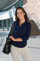 Business woman walking outside building, portrait