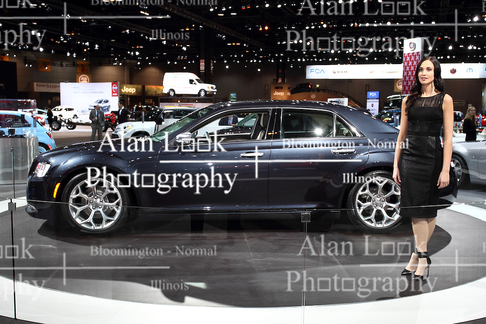 "12 February 2015:   A female model shows off a 2015 CHRYSLER 300: MoPar fans visiting the 2015 Chicago Auto Show will be checking out the many refinements to the 2015 Chrysler 300 four-door sedan. Visually, the body is even more sculptural and expressive with bolder front grille, signature LED lighting, unique finishes and new wheel designs. Finishing the new 300 sedan's powerful rear stance is a new sculpted LED taillamp with an illuminated halo. All-new five-passenger interior includes a standard seven-inch full-color driver info display and class-exclusive electronic rotary transmission shifter. The popular Chrysler 300 is available in four highly equipped models: 300 Limited, 300S, 300C and 300C Platinum. The Chrysler 300 SRT8 is covered separately. For 2015, the Chrysler 300S combines an even more ""blacked out"" look and new Ambassador Blue sport interior, with benchmark levels of quality, technology and craftsmanship. Large 20-inch polished-face wheels are for rear-wheel drive only, and the 19-inch with all-wheel drive, provides the sedans with an even more planted and road-holding look. Also, the Chrysler 300 AWD model offers even more all-season capability, and includes an exclusive active transfer case and front-axle disconnect for greater fuel economy. New 2015 Chrysler 300 rear-wheel drive or AWD models with the 292 horsepower (300 horsepower on 300S model) 3.6-liter Pentastar V-6 engine continue to use the TorqueFlite eight-speed transmission. Optional powerplant on all 300 models is the 363-hp 5.7L Hemi V-8. Beats by Dr. Dre audio technology that includes a 522-watt 12-channel amplifier is standard on the Chrysler 300S and available on other 300 models. Every '15 Chrysler 300 variant is outfitted with a tailored trunk that can handle 16.3 cubic feet of luggage.<br /> <br /> First staged in 1901, the Chicago Auto Show is the largest auto show in North America and has been held more times than any other auto exposition on the continent. The 2015 show marks the"