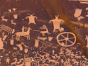 Newspaper Rock State Historic Monument, Utah, USA. The Wingate sandstone cliffs that enclose the upper end of Indian Creek Canyon are covered by hundreds of ancient Indian petroglyphs (rock carvings), one of the largest, best preserved and accessible groups in the Southwest USA. The petroglyphs have a mixture of human (feet, figures), animal (deer, pronghorn, horse), material and abstract forms of uncertain meaning. Starting about 2000 years ago, humans have chipped away the dark natural desert varnish to reveal lighter colored sandstone beneath.