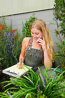 Young woman talking on her cell phone in a garden / nursery writing on a clip board