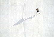 Man repelling down white wall with line and shadow