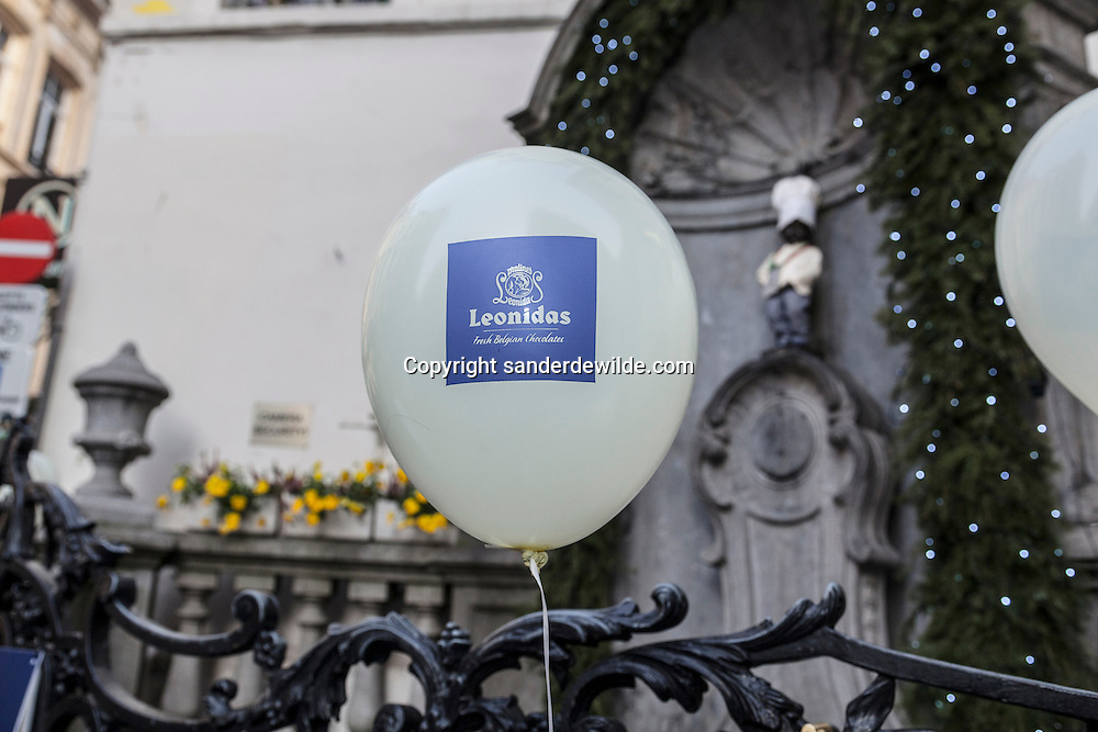 Brussels, Belgium, 2012 19 December. Belgian chocolate brand Leonidas starts celebrating its 100 years exitence in 2013. At the famous Belgian medieval statue Manneken Pis (peeing man) people gathered today.A balloon with the Leonidas log in front of the manneken pis statue.