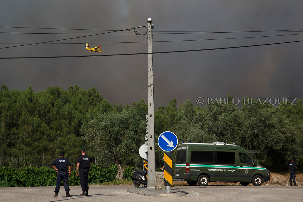 LEIRIA, PORTUGAL - JUNE 20:  Police controls the access to an area where allegedly firefighter plane crashed as a firefighter plane flies over on June 20, 2017 near Picha, in Leiria district, Portugal. On Saturday night, a forest fire became uncontrollable in the Leiria district, killing at least 62 people and leaving many injured. Some of the victims died inside their cars as they tried to flee the area.  (Photo by Pablo Blazquez Dominguez/Getty Images)