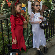 Young girls dressed as the devil and angle costumes for trick-or-treat on Halloween day in Greenwich Village in NYC..