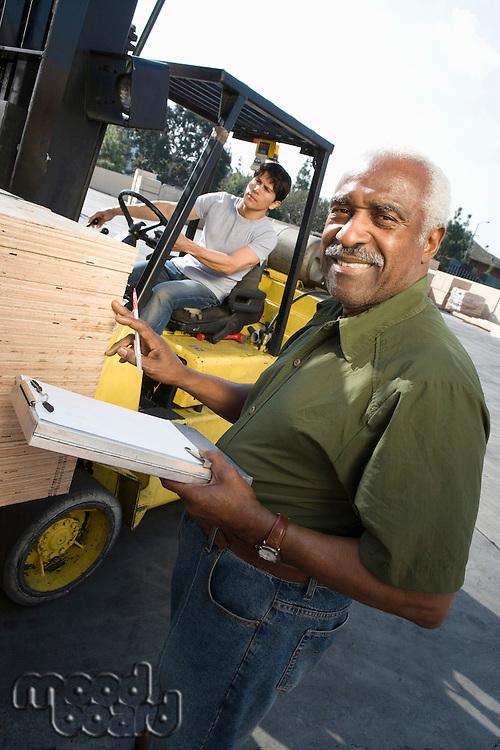 Senior warehouseman and mid-adult forklift truck driver