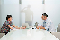 Man and woman talk over conference table man on mobile phone visible through translucent office wall