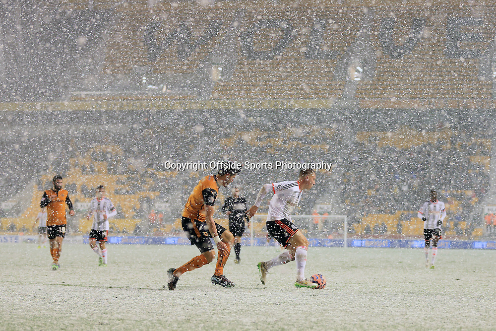 13th January 2015 - FA Cup - 3rd Round Replay - Wolverhampton Wanderers v Fulham - Danny Batth of Wolves challenges Cauley Woodrow of Fulham in the driving snow - Photo: Simon Stacpoole / Offside.