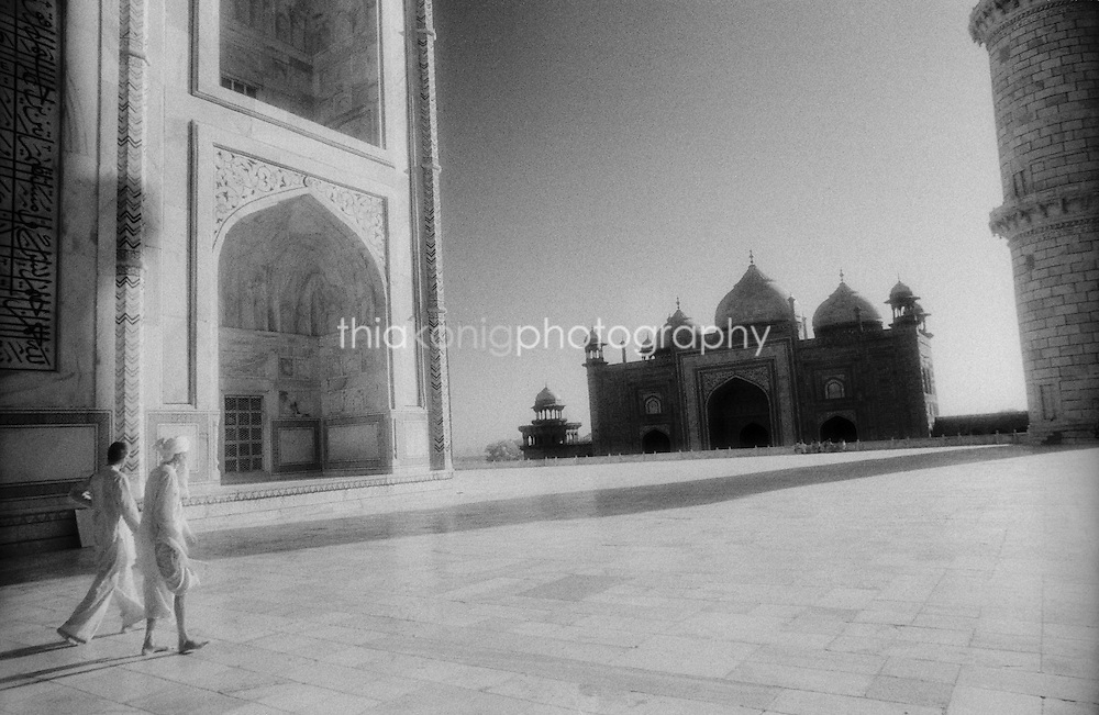 A young man and old man walk into the frame at the Taj Mahal, India