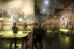 Visitors looking at exhibits are seen through a glass display at Shaoshan Mao Zedong Memorial Museum in Shaoshan, Hunan Province in central China, 28 April 2016. Shaoshan is the hometown of former Communist leader Mao Zedong, popularly known as Chairman Mao. Thousands of visitors descend on this small Chinese town burrowed in the hills of Central China's Hunan province to pay homage to the great helmsman everyday. It is one of the core sites of the 'Red Tourism' industry, where communist party cadres and ordinary Chinese tourists alike seek to relive the experiences and rekindle the spirit of the revolutionaries.