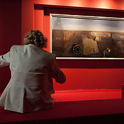 "MILAN, ITALY - SEPTEMBER 21:  A woman sits in front of ""The Search for the fourth dimension"", oil painting by Salvador Dali at the Exhibition preview at Palazzo Reale on September 21, 2010 in Milan, Italy. Dali is back in Milan with Il sogno si avvicina, an exhibition that takes place at Palazzo Reale  and that focus on the relationship between the great Spanish artist's visions and his favourite themes:  landscape, dream and desire."