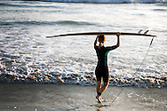Female surfer entering ocean carrying surfboard over her head at Terramar Beach in Carlsbad,CA.