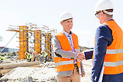 Engineers shaking hands at construction site against clear sky
