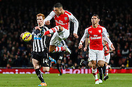 Alex Oxlade-Chamberlain of Arsenal passes the ball under pressure from Jack Colback of Newcastle United (left) as Kieran Gibbs of Arsenal (right) looks on during the Barclays Premier League match at the Emirates Stadium, London<br /> Picture by David Horn/Focus Images Ltd +44 7545 970036<br /> 13/12/2014