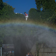 Spray from a power washer kicks up a small rainbow and keeps the dust down.