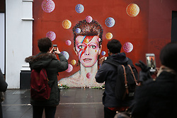 © Licensed to London News Pictures. 11/01/2016. London, UK. People gather at a mural to David Bowie in Brixton. The Death of David Bowie has been announced. Bowie was born in Brixton.  Photo credit: Peter Macdiarmid/LNP