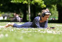 © Licensed to London News Pictures. 14/05/2019. London, UK. A woman reads on her mobile phone on a warm and sunny day London's St James's Park. Temperatures are set to reach 19C in the capital and potentially higher in the some parts of the UK. Photo credit: Dinendra Haria/LNP