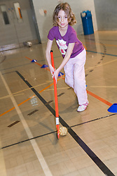 Young girl playing a game of indoor hockey in the sports hall of her local leisure centre,