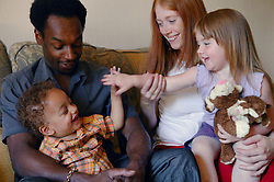 Multiracial family group sitting together on the settee,
