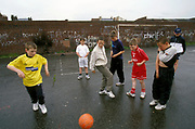 Kids playing football on a concrete football pitch, UK, 2000