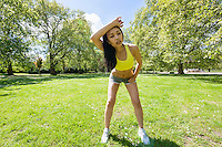 Full length of tired young woman looking away while exercising in park