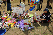 Aurora CO 21 June 2012: In #27 jersey, SHELLY FRADKIN, sits at a memorial for ALEX SULLIVAN, one of 12 killed in theatre shooting, ironically on his birthday (cards at memorial). Fradkin knew Alex well? he soon was one of his best friends. (The #27 jersey is of DArren Williams (cq) Denver Bronco who was shot and killed in a crime). FRADKIN holds at times a photo of SULLIVAN. Memorial is across the street (Sable St) from the theatre