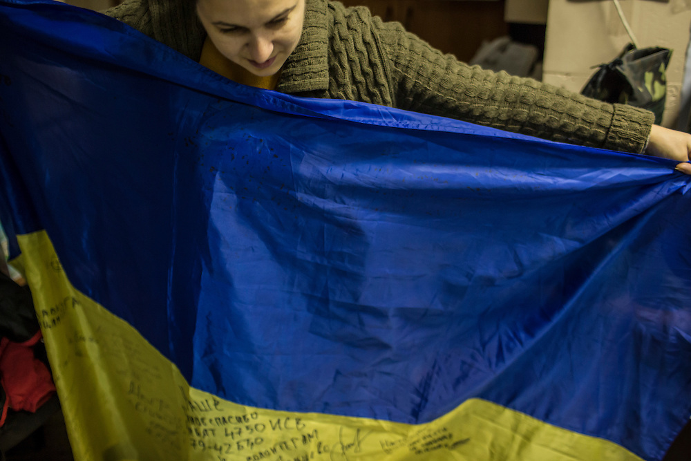 DNIPROPETROVSK, UKRAINE - NOVEMBER 16, 2014:  Natalia Naumenko, 38, the owner of a travel agency, holds a flag which has been signed by soldiers serving all along the front lines at the Dnipropetrovsk Volunteer Logistics Center, a charity organization that produces supplies for pro-Ukrainian fighters battling rebels in the country's East, in Dnipropetrovsk, Ukraine. When volunteers deliver supplies to soldiers, they bring the flag with them to be signed. CREDIT: Brendan Hoffman for The New York Times