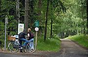Nederland, Herkenbosch, 10-6-2010Recreanten op de fiets bekijken een kaartje van de omgeving in nationaal park de meinweg.Foto: Flip Franssen/Hollandse Hoogte