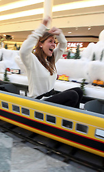 23 November 2012. New Orleans, Louisiana,  USA. <br /> Christmas time at the Mall. An excited mother rides the Christmas Grotto train on Black Friday.<br /> Photo; Charlie Varley/varleypix.com