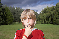 Portrait of boy (7-9) blowing whistle in meadow