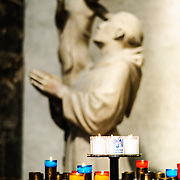 Votives in the Cathedral de Reims with statue of monk and child in the background