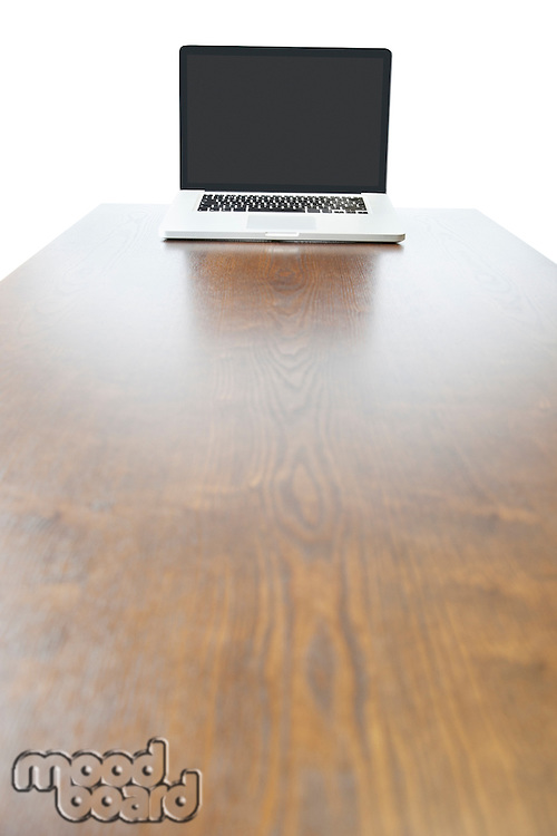 Laptop at the end of wooden table