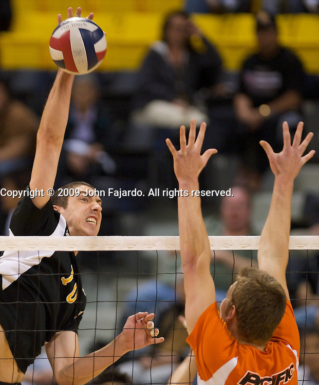 Luke Shea hits at the block of Sean Daley(13) in the Mountain Pacific Sports Federation match against Pacific at the Walter Pyramid, Long Beach CA, Saturday, April 4, 2009.  Long Beach State wins the match in five sets 29-31, 30-13, 25-30, 30-21, 15-8.