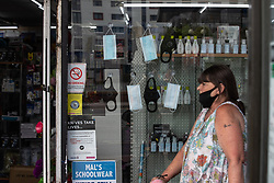 © Licensed to London News Pictures .  07/05/2020 . Salford, UK. A women wearing a mask over her mouth walks past a shop with facemasks hanging in the window , on Hankinson Way in Salford . Photo credit : Joel Goodman/LNP